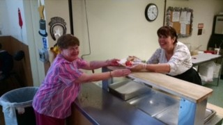 Kitchen volunteer serving a meal to a senior meal participant